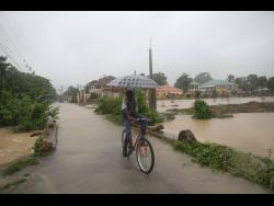 Carlos Robinson of Duke Street, Toll Gate, Clarendon, makes his way through the flooded streets of his community yesterday.