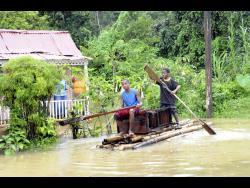 In this 2010 photo, two teen boys use a raft to traverse the floodwaters in their home community of Chigwell in Hanover.