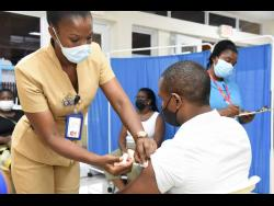 Public health nurse Natasha Bently vaccinates Winston Grant  during a vaccination drive at the University Hospital of the West Indies last Thursday.