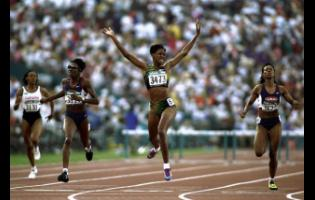 Deon Hemmings raises her arms aloft as she crosses the line to win the 400 metres hurdles final during the 1996 Olympic Games at the Olympic Stadium in Atlanta, Georgia, USA.