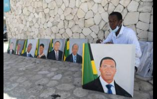 Linstead artist Nigel Easy shows off his paintings of popular figures in the Jamaican Government, outside the Jamaica Conference Centre on Tuesday.