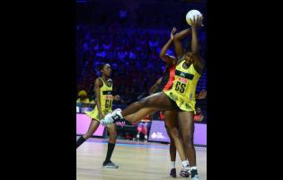 Jamaica goal shooter Jhaniele Fowler (right) acrobatically grabs a pass while her teammate Shanice Beckford looks on, during their Vitality Netball World Cup fifth-place play-off at the M&S Bank Arena in Liverpool, England, July 21, 2019.