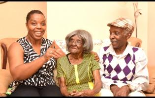 1. Ivy Allen (centre) listens keenly to her granddaughter Carla Silvera-Cox. Looking on is Allen's son Morris Henry.