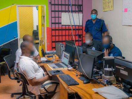 Staff Officer Peter Jarrett monitors the four inmates currently enrolled at the University of the Commonwealth Caribbean as they participate in an online class from the St Catherine Adult Correctional Centre's Computer Lab.